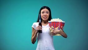 有玉米花观看可怕电影的杯子的震惊妇女,拿着泡沫腾涌的水 图库摄影