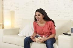 有玉米花观看的电视的愉快的妇女在沙发长沙发愉快的激动的享用的喜剧电影 图库摄影