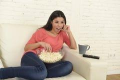 有玉米花观看的电视的愉快的妇女在沙发长沙发愉快的激动的享用的喜剧电影 免版税库存图片
