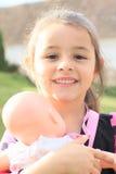 有玩偶的微笑的女孩 免版税图库摄影