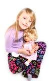 有玩偶的逗人喜爱的小女孩坐空白背景 库存图片