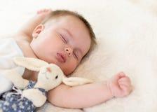 有玩具兔宝宝的逗人喜爱的矮小的婴孩在家睡觉在床上的 免版税库存图片