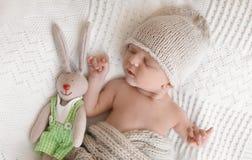 有玩具兔宝宝说谎的可爱的新生儿 免版税库存照片