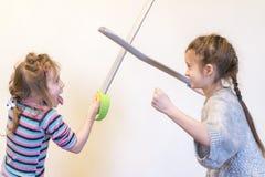 有玩具剑戏剧骑士的两个女孩 Children& x27; s情感 免版税库存图片