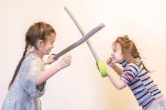 有玩具剑戏剧骑士的两个女孩 Children& x27; s情感 免版税图库摄影