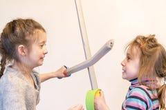 有玩具剑戏剧骑士的两个女孩 Deyochki争论并且生气 冲突 库存照片