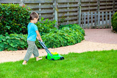 有玩具割草机的小男孩 免版税库存图片