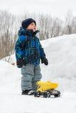 有玩具卡车的男孩在深Snowbank旁边 库存照片