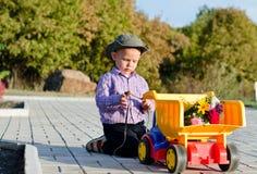 有玩具卡车的逗人喜爱的小男孩 免版税库存照片