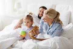 有玩具和父母的愉快的孩子在床上在家 库存图片