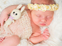 有玩具和头饰带的美丽的睡觉的新出生的女孩 库存照片