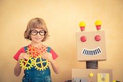 有玩具机器人的滑稽的书呆子孩子 免版税库存图片