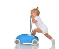 有玩具步行者的逗人喜爱的微笑的女婴小孩做第一步 免版税库存图片