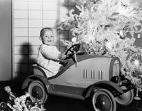有玩具汽车的孩子在圣诞树下(所有人被描述不更长生存,并且庄园不存在 供应商保单tha 免版税库存照片
