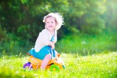 有玩具汽车的愉快的小孩女孩在庭院里 免版税库存照片