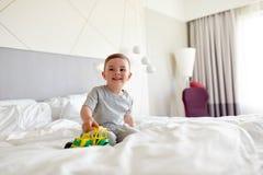 有玩具汽车的愉快的小男孩在家或旅馆床上 免版税图库摄影