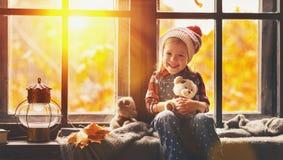 有玩具注视着通过窗口的玩具熊的儿童女孩自然 免版税库存图片