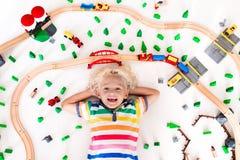 有玩具火车的孩子 哄骗木铁路 免版税库存照片
