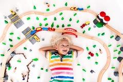 有玩具火车的孩子 哄骗木铁路 免版税库存图片