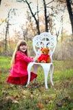 有玩具熊和椅子的愉快的小女孩 免版税图库摄影