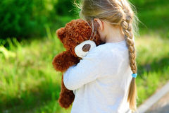 有玩具熊的可爱的哀伤的女孩在公园 免版税库存照片