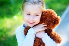 有玩具熊的可爱的小女孩在公园 库存照片