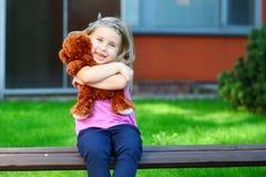 有玩具熊的可爱的小女孩在公园 免版税库存照片