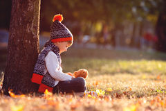 有玩具熊的可爱的小男孩在公园在秋天天 库存图片
