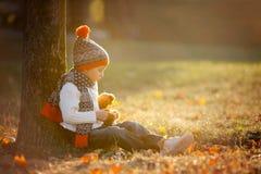 有玩具熊的可爱的小男孩在公园在秋天天 免版税库存照片
