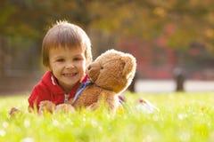 有玩具熊的可爱的小男孩在公园 免版税图库摄影