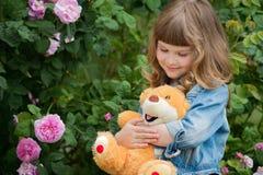 有玩具熊的可爱的微笑的女孩在有桃红色玫瑰的公园 免版税库存照片