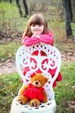 有玩具熊的女孩和一把椅子在森林里 免版税库存图片