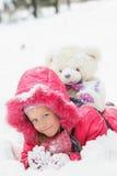 有玩具熊的女孩在冬天森林里 免版税库存照片