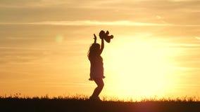 有玩具熊的小女孩在日落 拿着熊玩偶熊的剪影女孩观看日落 概念大梦想 影视素材
