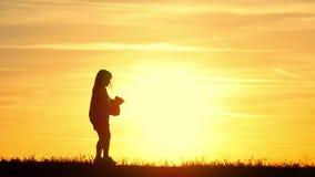 有玩具熊的小女孩在日落 拿着熊玩偶熊的剪影女孩观看日落 概念大梦想 股票视频