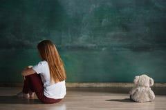 有玩具熊的小女孩坐地板在空的屋子里 孤独性概念 库存图片
