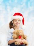 有玩具熊的微笑的小女孩 免版税库存图片