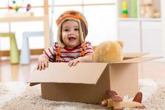 有玩具熊的微笑的试验飞行员男婴戏弄在纸板箱的戏剧 库存图片