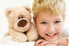 有玩具熊的快乐的小男孩是愉快和微笑 特写镜头 库存照片