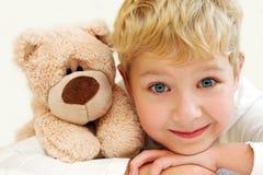 有玩具熊的快乐的小男孩是愉快和微笑 特写镜头 免版税库存照片