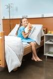 有玩具熊的患者坐床在医院 库存图片