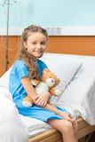 有玩具熊的患者坐床在医院 库存照片