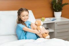 有玩具熊的患者坐床在医院 免版税库存图片