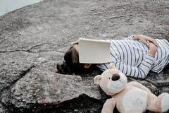 有玩具熊的愉快的亚裔孩子本质上,在度假放松时间 库存图片