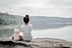 有玩具熊的愉快的亚裔孩子本质上,在度假放松时间 免版税库存照片
