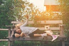 有玩具熊的愉快的亚裔孩子本质上,在度假放松时间 库存照片