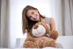 有玩具熊的愉快的妇女 库存照片