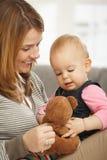 有玩具熊的愉快的妈咪和婴孩 库存照片