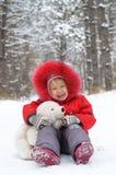 有玩具熊的愉快的孩子在雪 免版税库存图片