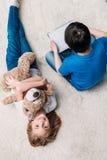 有玩具熊的有数字式片剂的女孩和男孩在地毯在家 库存照片